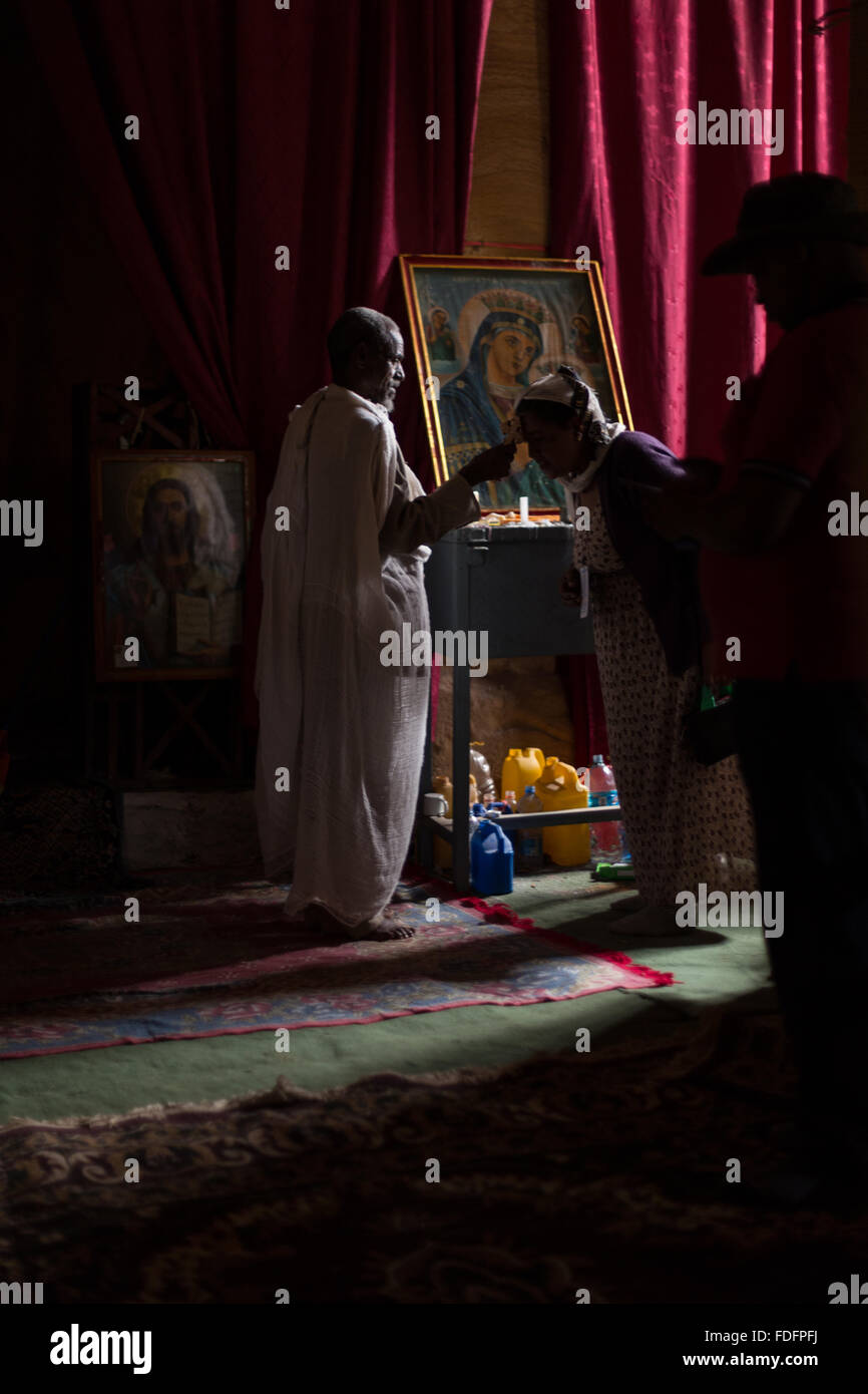 Red curtains catch the low light inside a stone-cut church near Mekele in Ethiopia Stock Photo