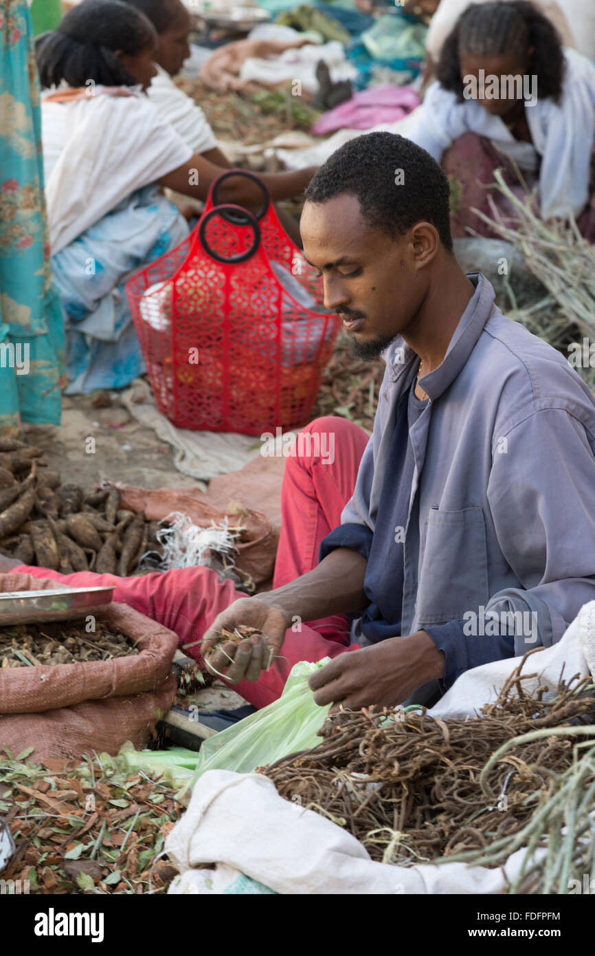 A man sorts bags of local produce in a busy market in Mekele, Ethiopia Stock Photo