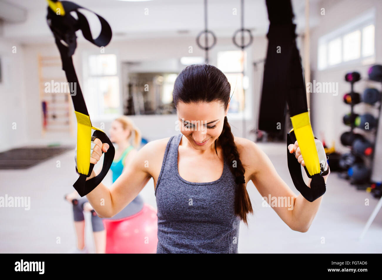 Woman in gym training arms with trx fitness strips Stock Foto
