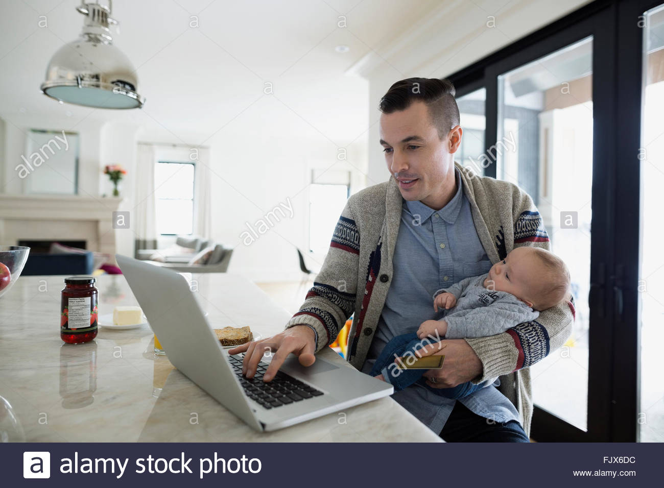 Father holding baby son and working at laptop Stock Photo