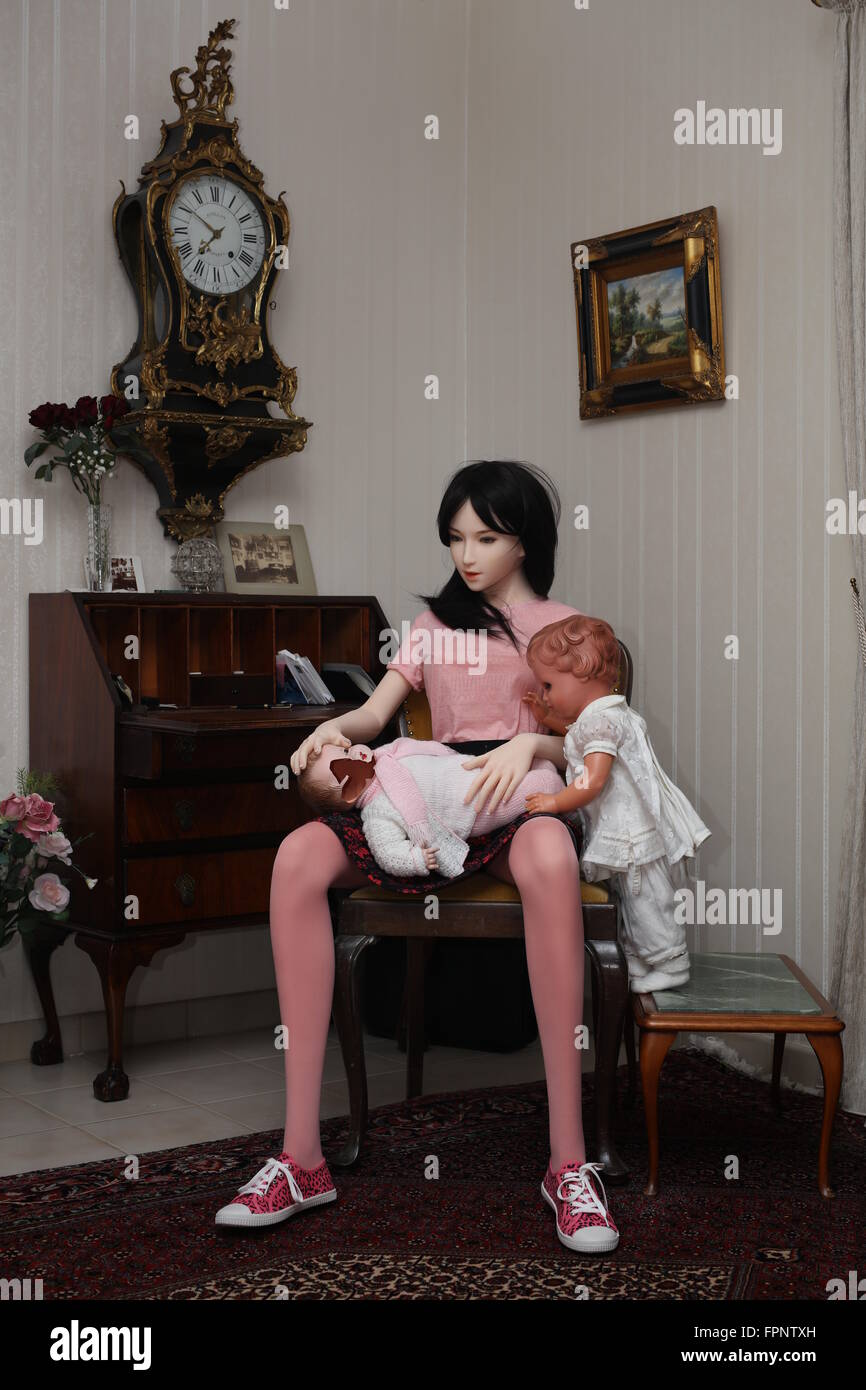 silicone-doll-sitting-on-chair-and-holdi