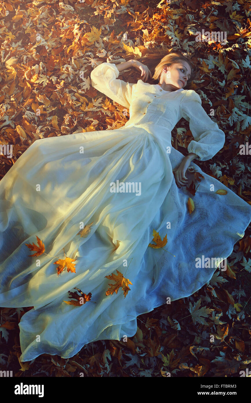 Beautiful woman with victorian dress on a bed of leaves. Sadness and loneliness concept Stock Foto