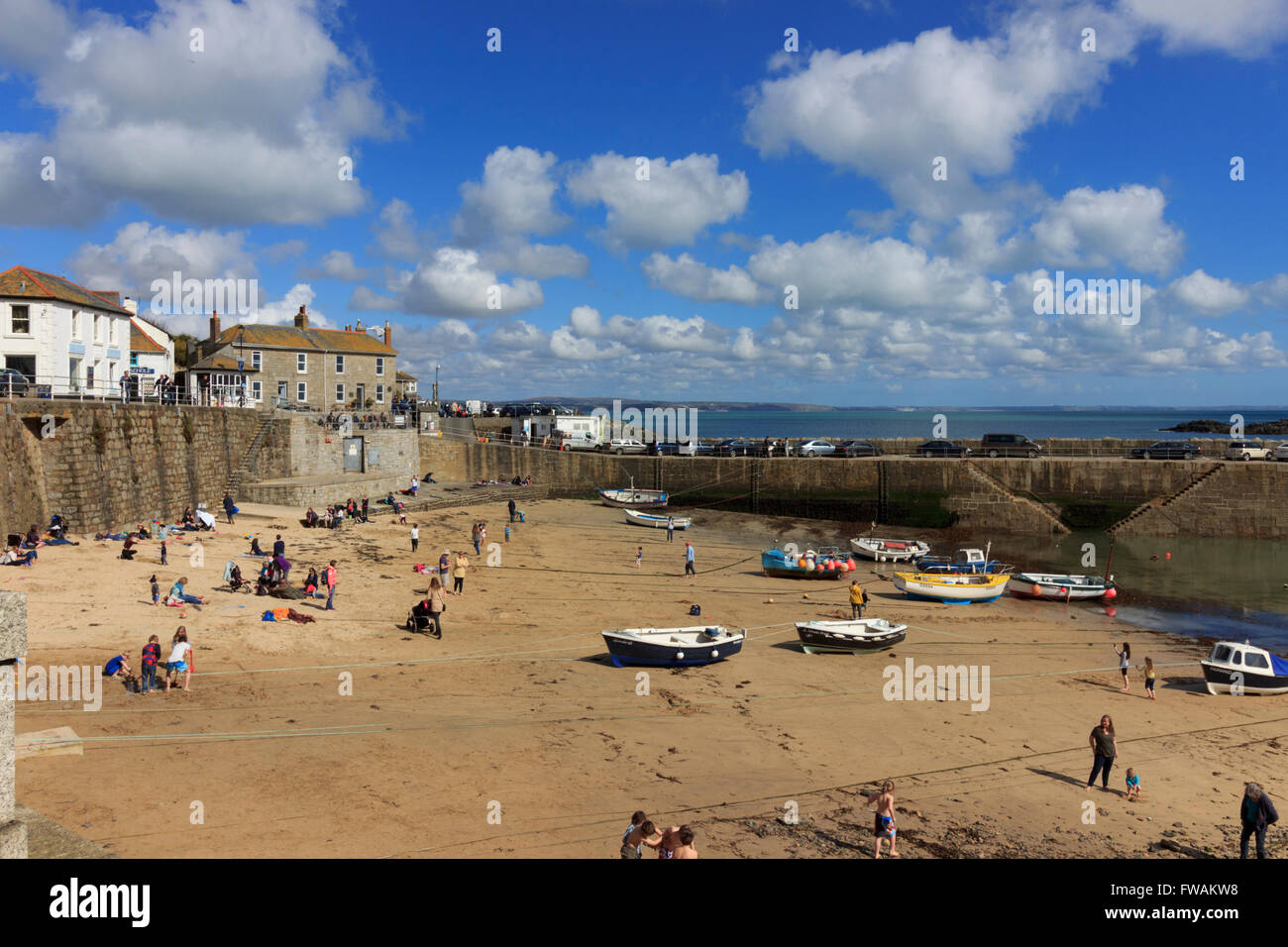 mousehole-cornwall-uk-harbour-and-beach-with-fishing-boats-pulled-FWAKW8.jpg