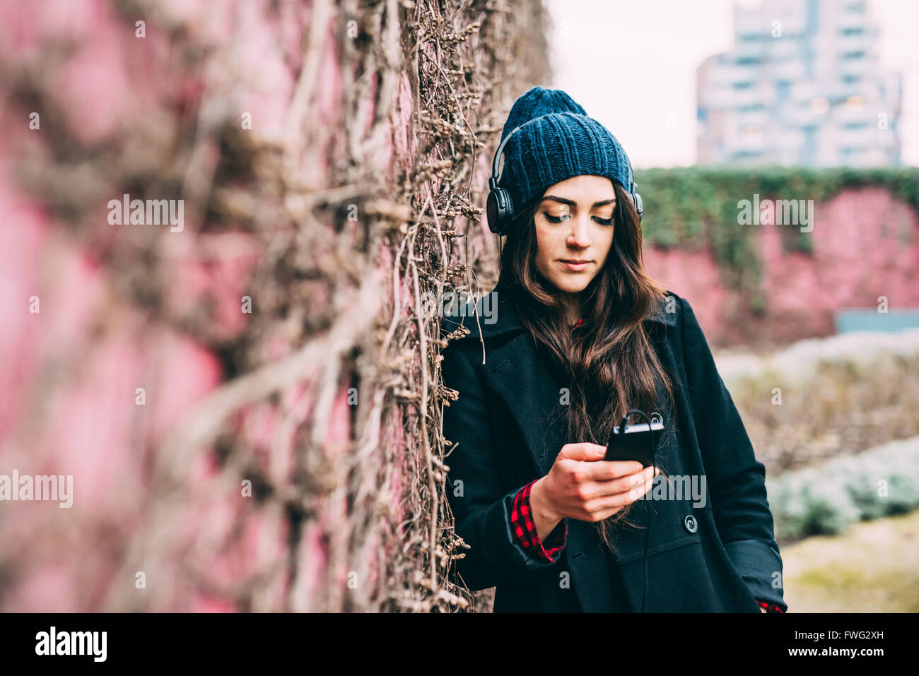 Half length of young beautiful caucasian woman listening music with headphones and smart phone hand hold, looking Stock Photo