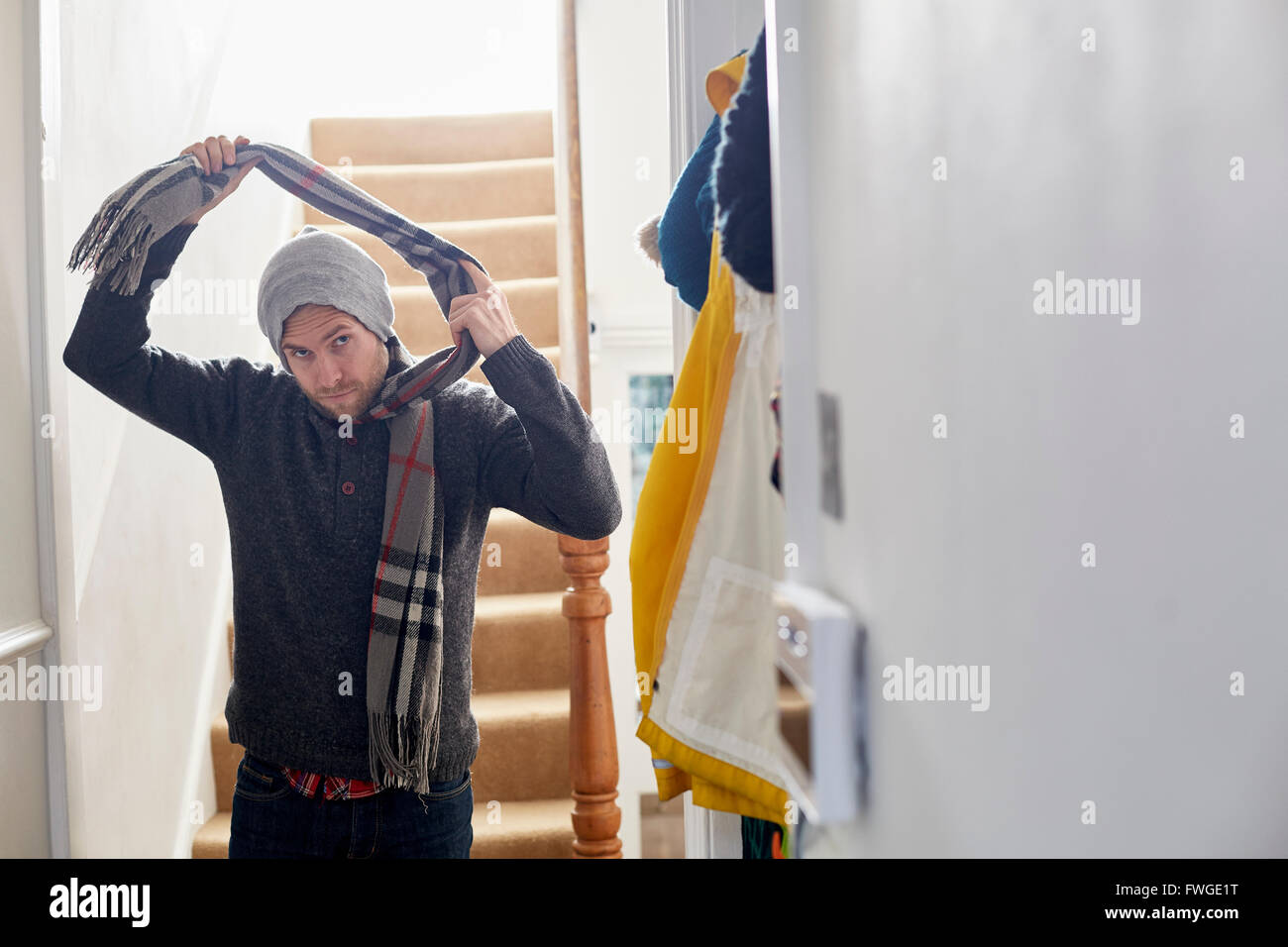 A man in a winter coat, hat and scarf arriving home, taking his scarf off. Stock Photo