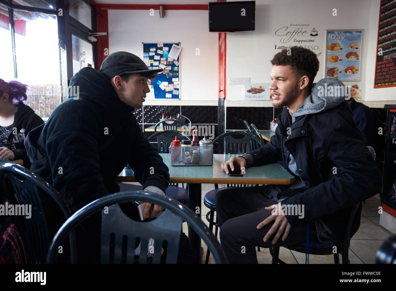 Two Male Students Eating Meal In Café Stock Foto