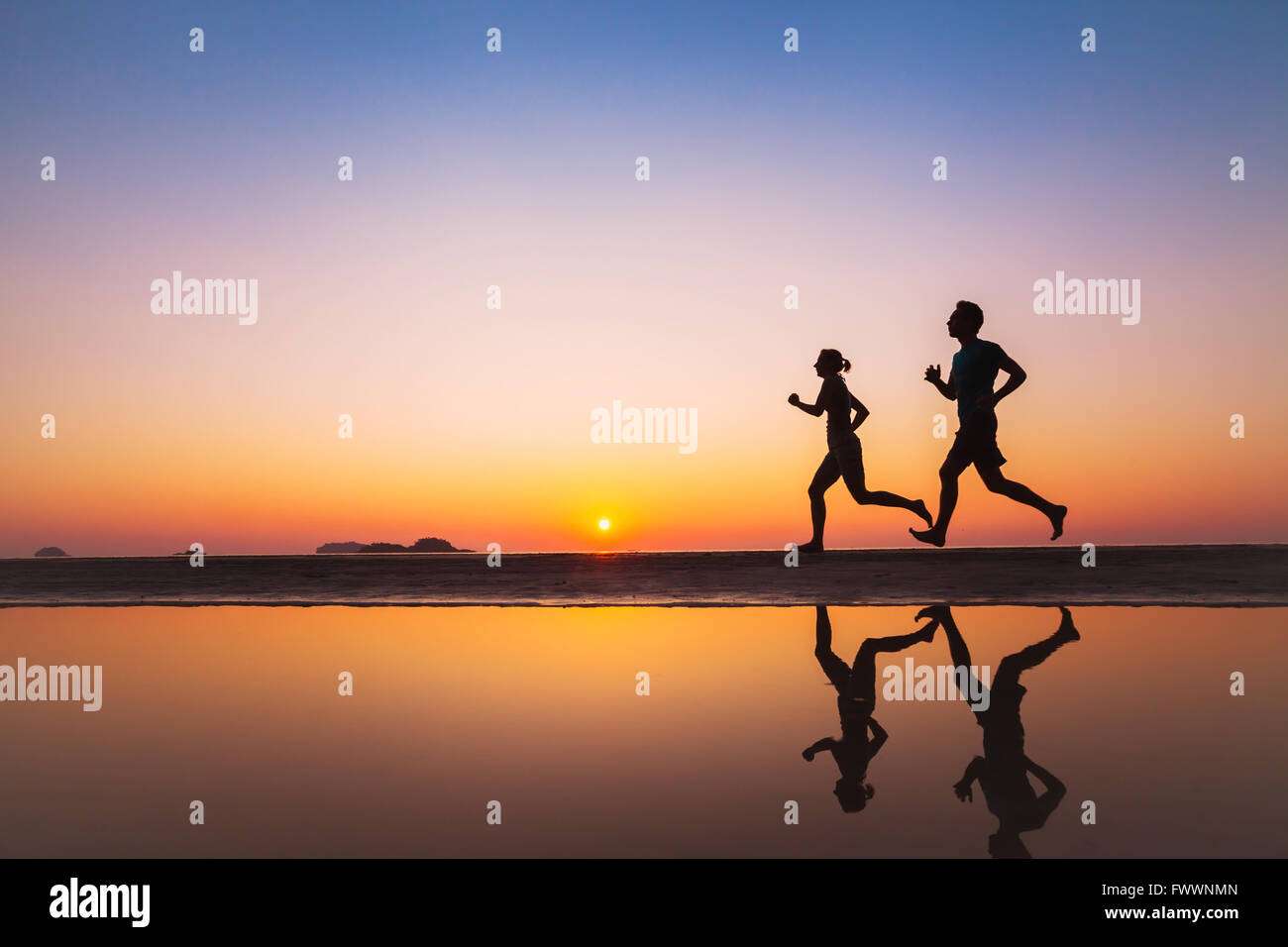 workout, silhouettes of two runners on the beach at sunset, sport and healthy lifestyle background Stock Foto