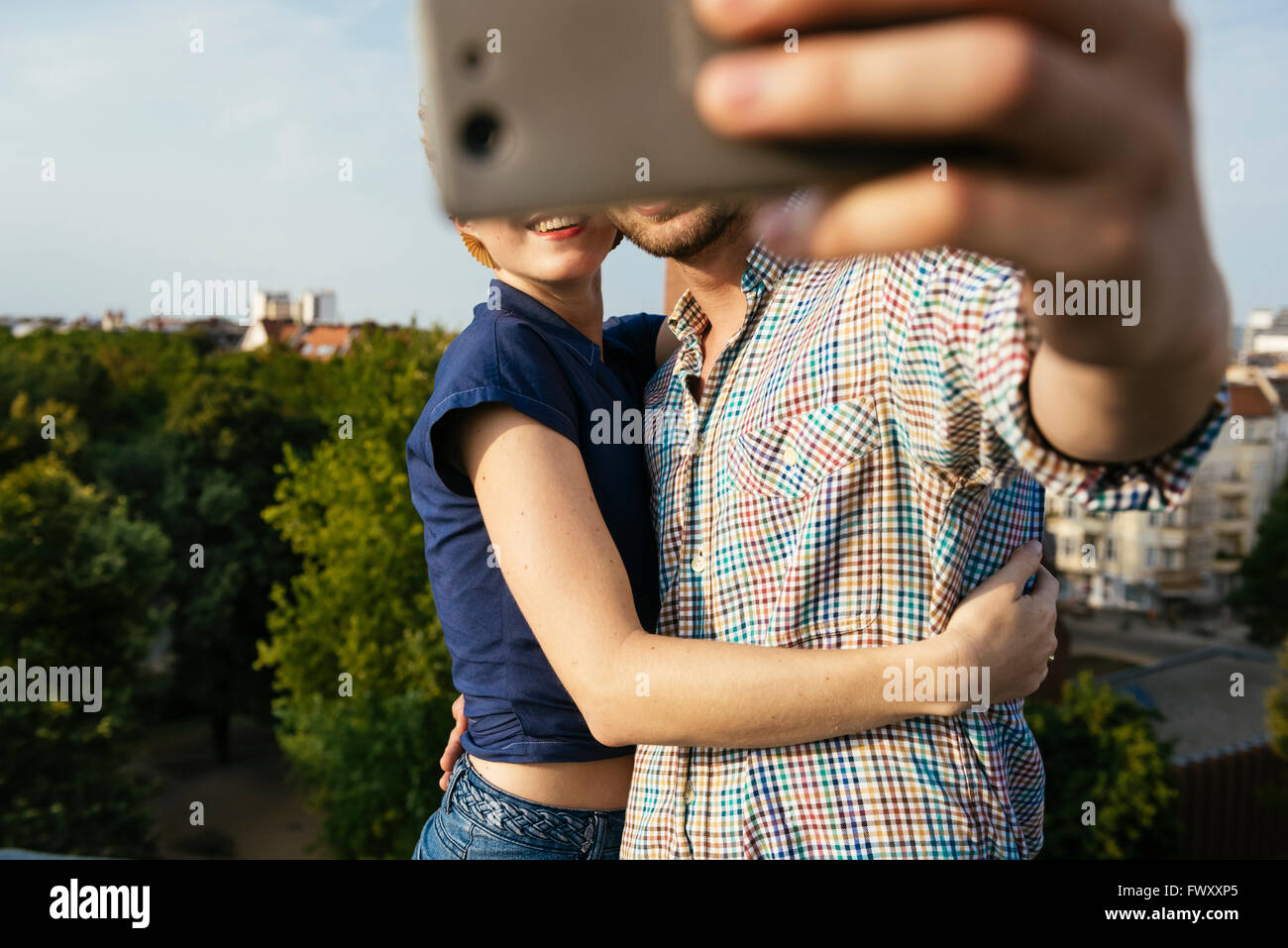 Germany, Berlin, Young couple hugging and taking selfie with smart phone Stock Foto