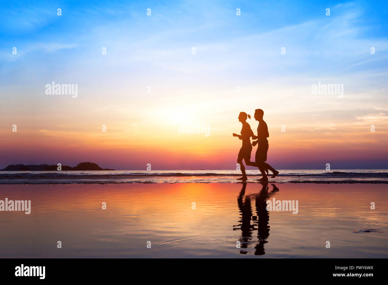 workout background, two people jogging on the beach at sunset, runners silhouettes, healthy lifestyle concept Stock Foto