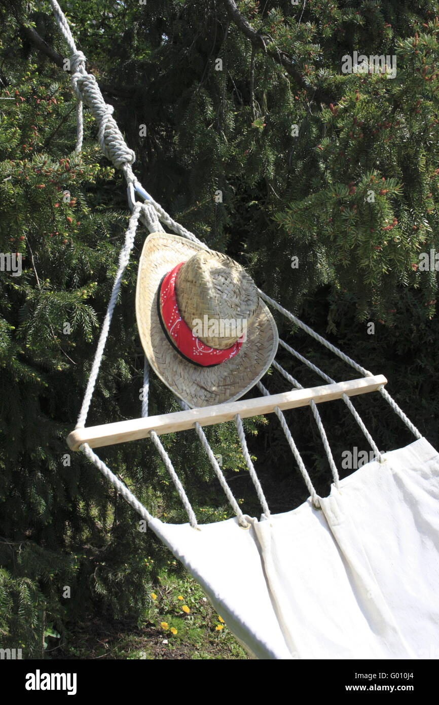Hammock and strawhat in garden Stock Photo