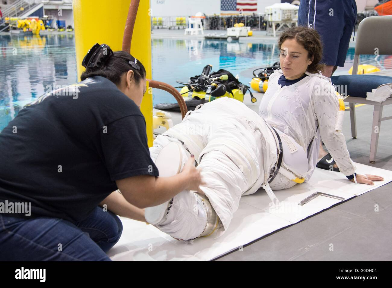 NASA astronaut Jessica Meir is assisted with her ...
