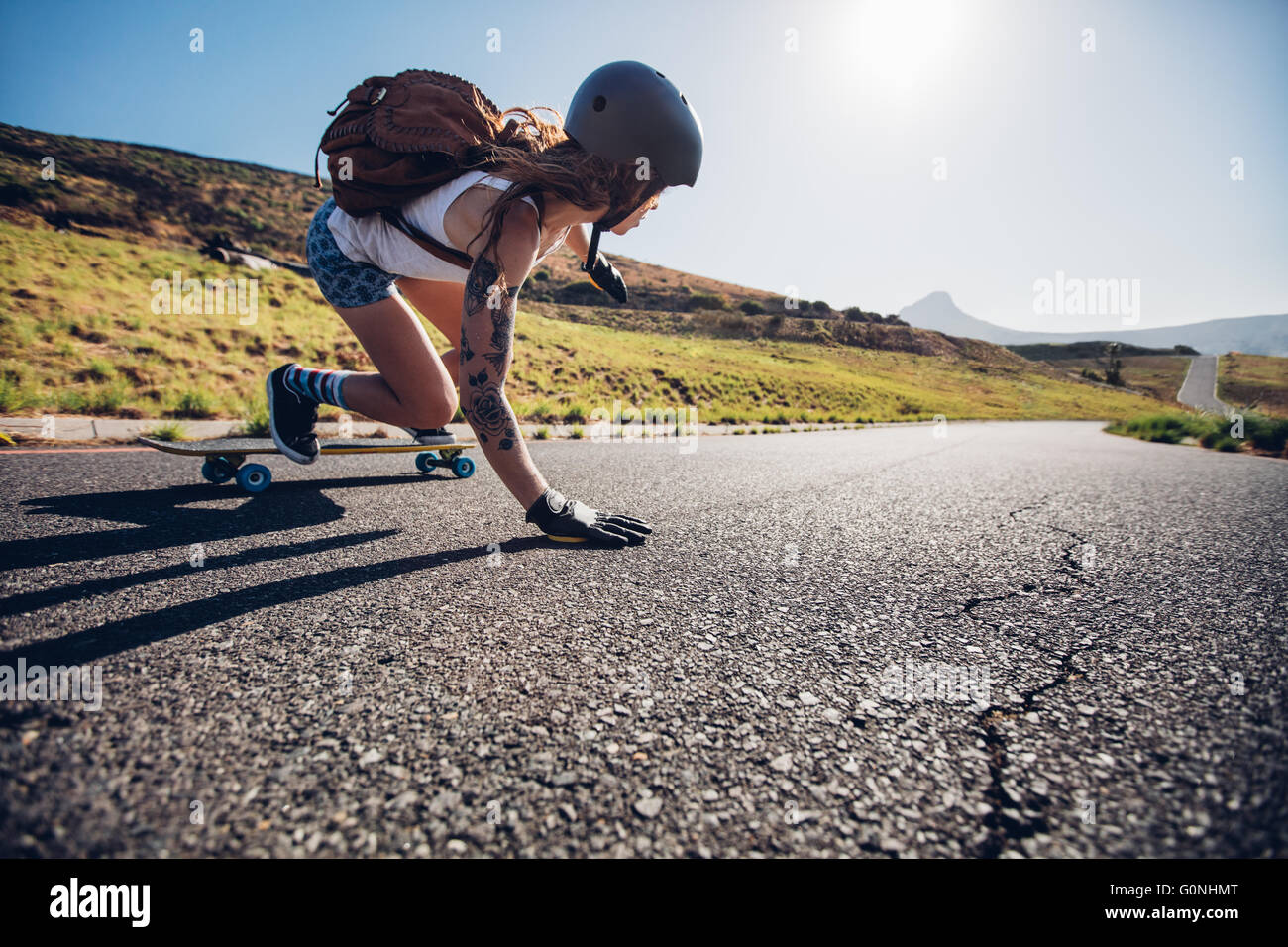 Young woman riding on her skateboard. Female skater practicing skating on country road. Stock Photo