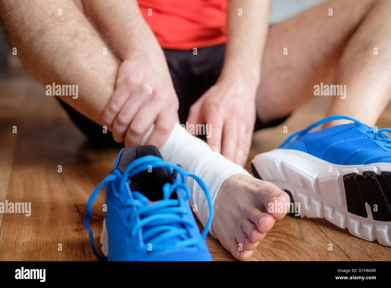 sportsman massaging his injured ankle after a sport accident Stock Foto