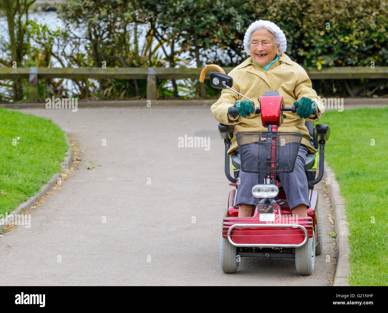 happy-elderly-lady-riding-a-mobility-scooter-in-a-park-G21NHF.jpg