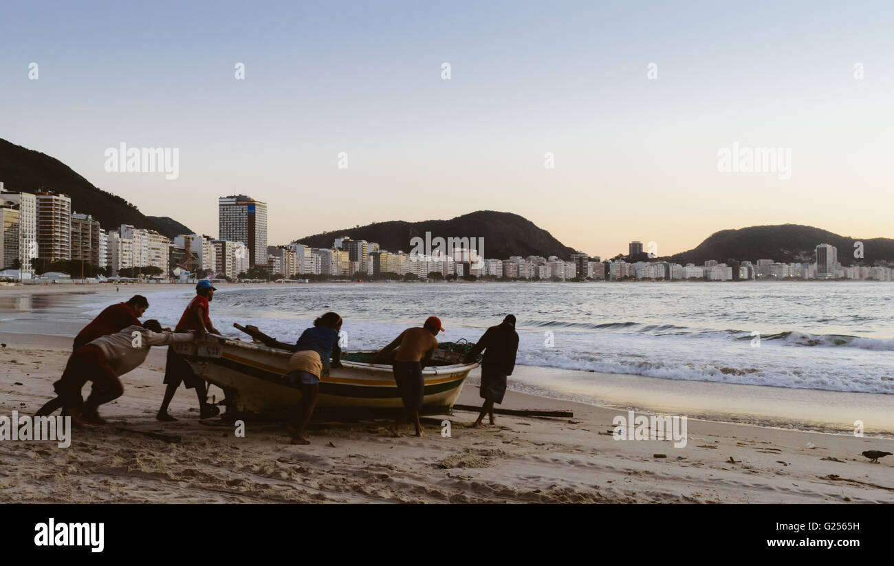 brazilian-fishermen-launch-a-brightly-painted-fishing-boat-on-a-tranquil-G2565H.jpg