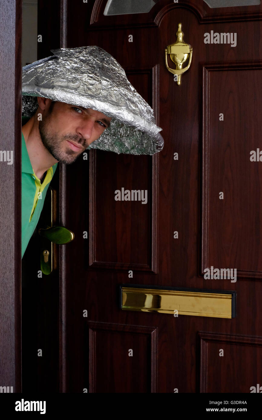 male conspiracy theory believer wearing tin foil hat peering out of doorway Stock Photo