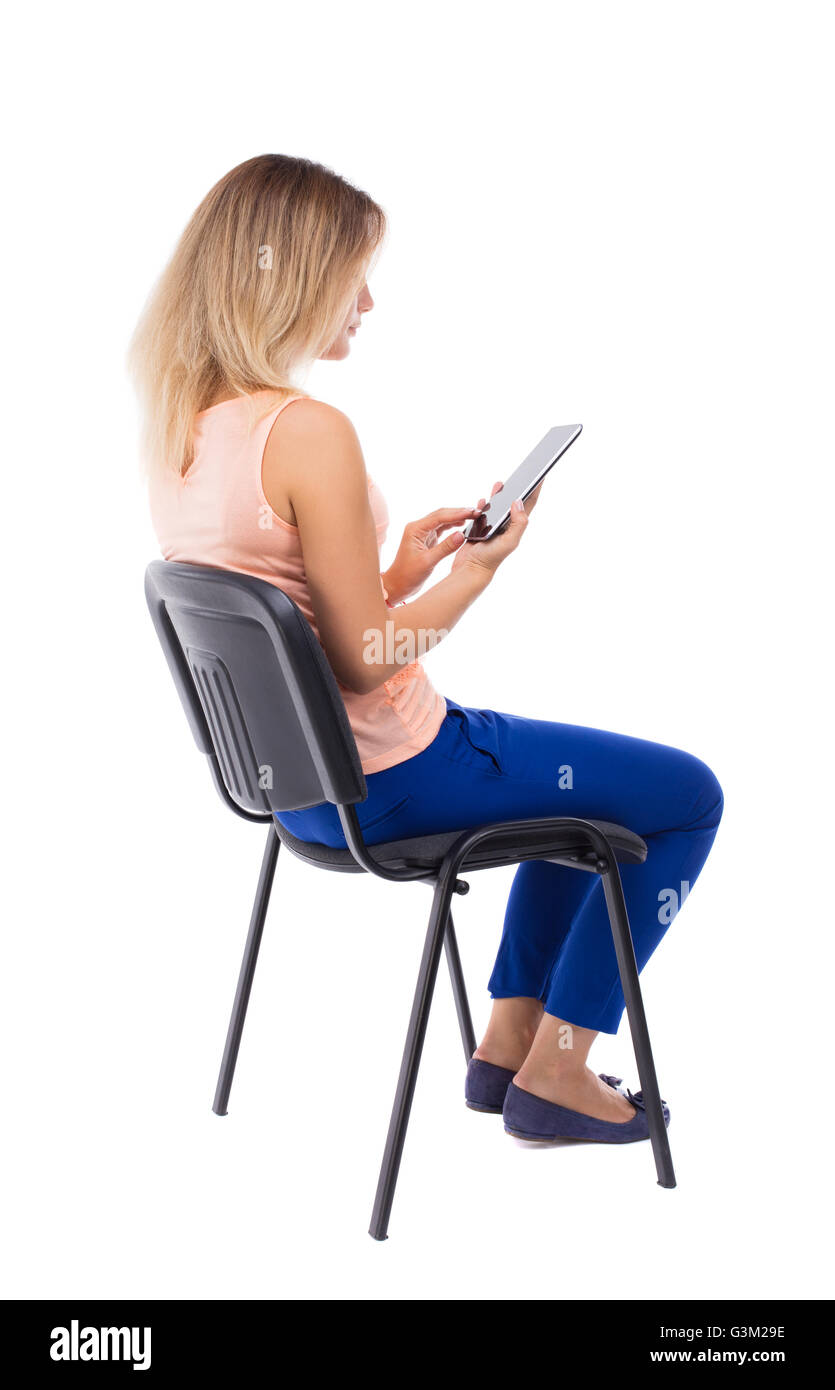 back view of woman sitting on chair and looks at the ...