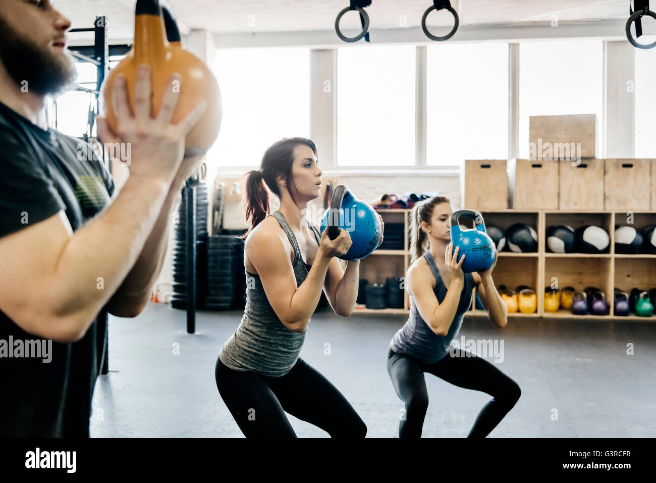 Germany, Young women and man cross training with kettlebells in gym Stock Foto