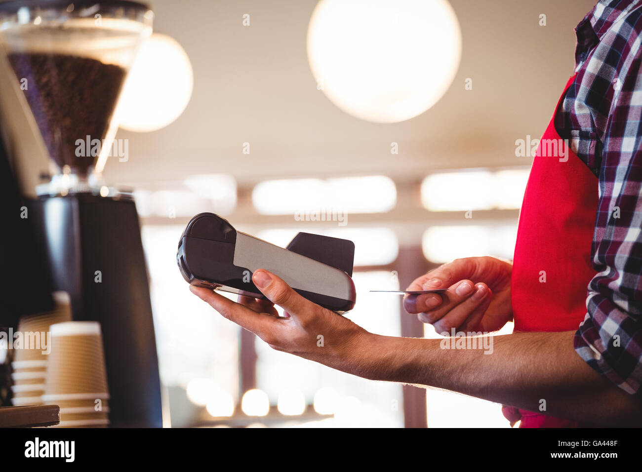 Waiter inserting customer's credit card into credit card machine Stock Photo