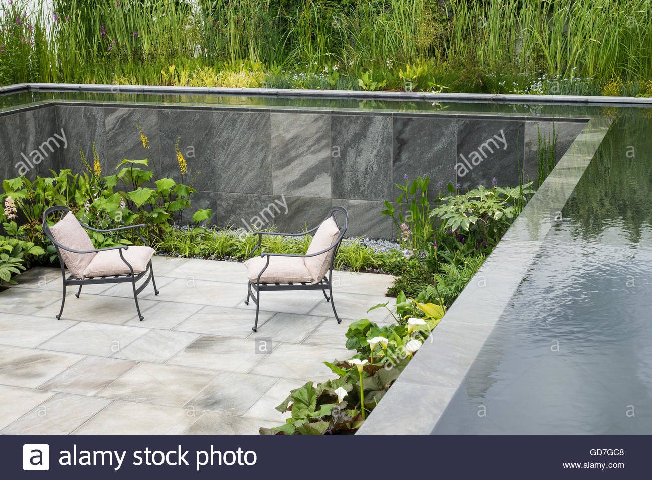Paved sunken garden with seats pool and cascading water for Pool and garden show