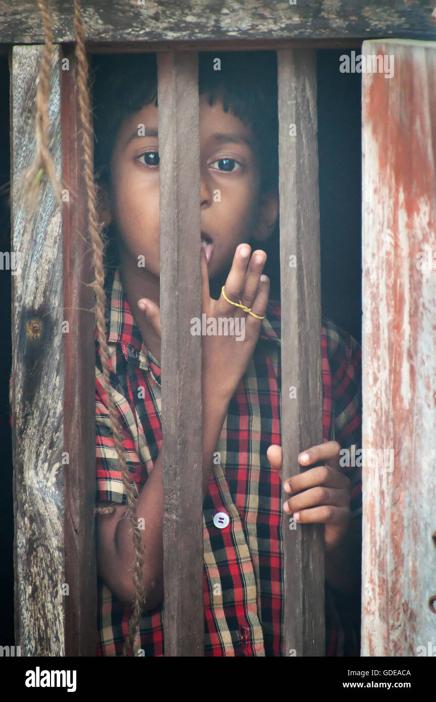 Unidentified Indian boy looks through a window at home in small fishing village Stock Photo