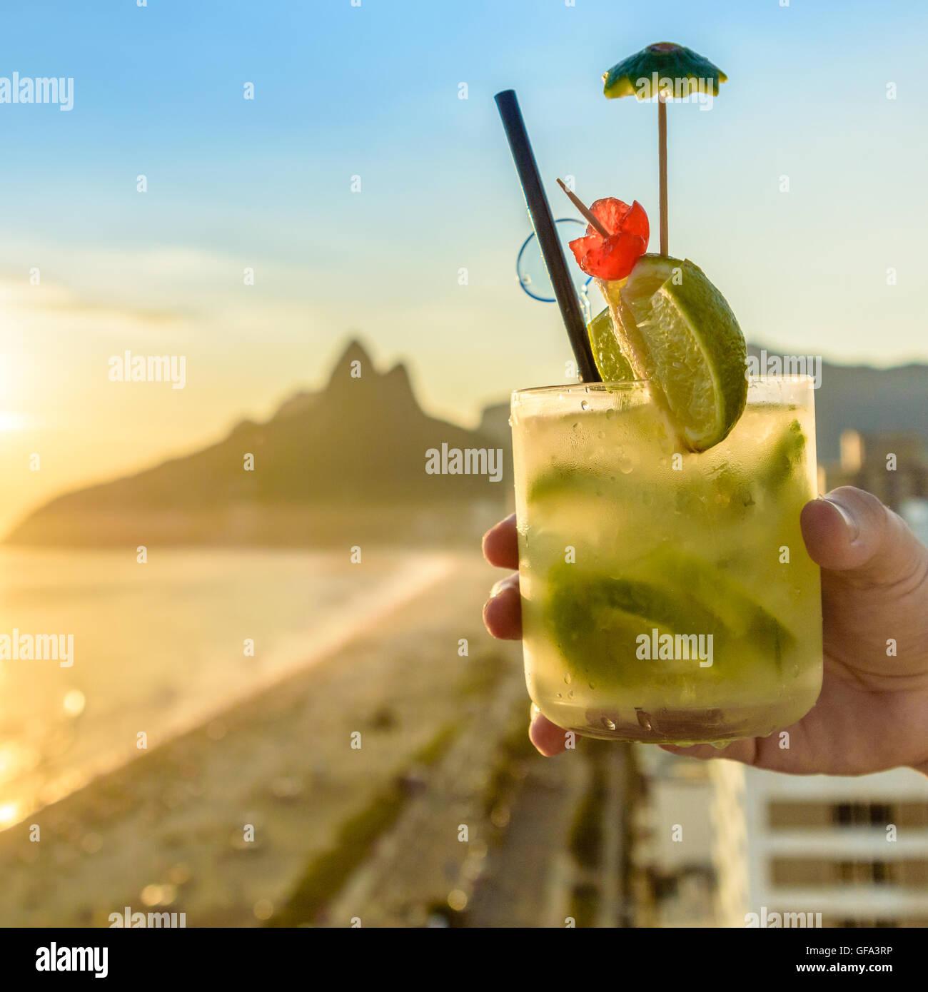 A delicious kiwi caipirinha drink overlooking the iconic Ipanema beach in Rio de Janeiro, Brazil Stock Photo