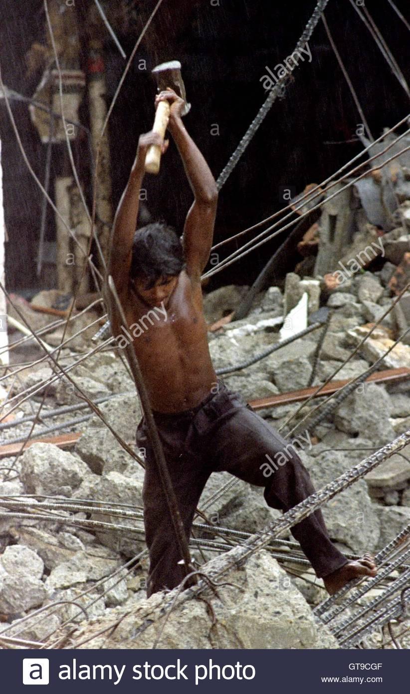 A workman breaks up concrete slabs at the Galadari Hotel in the Srilankan capital of Colombo November 13. The hotel Stock Photo