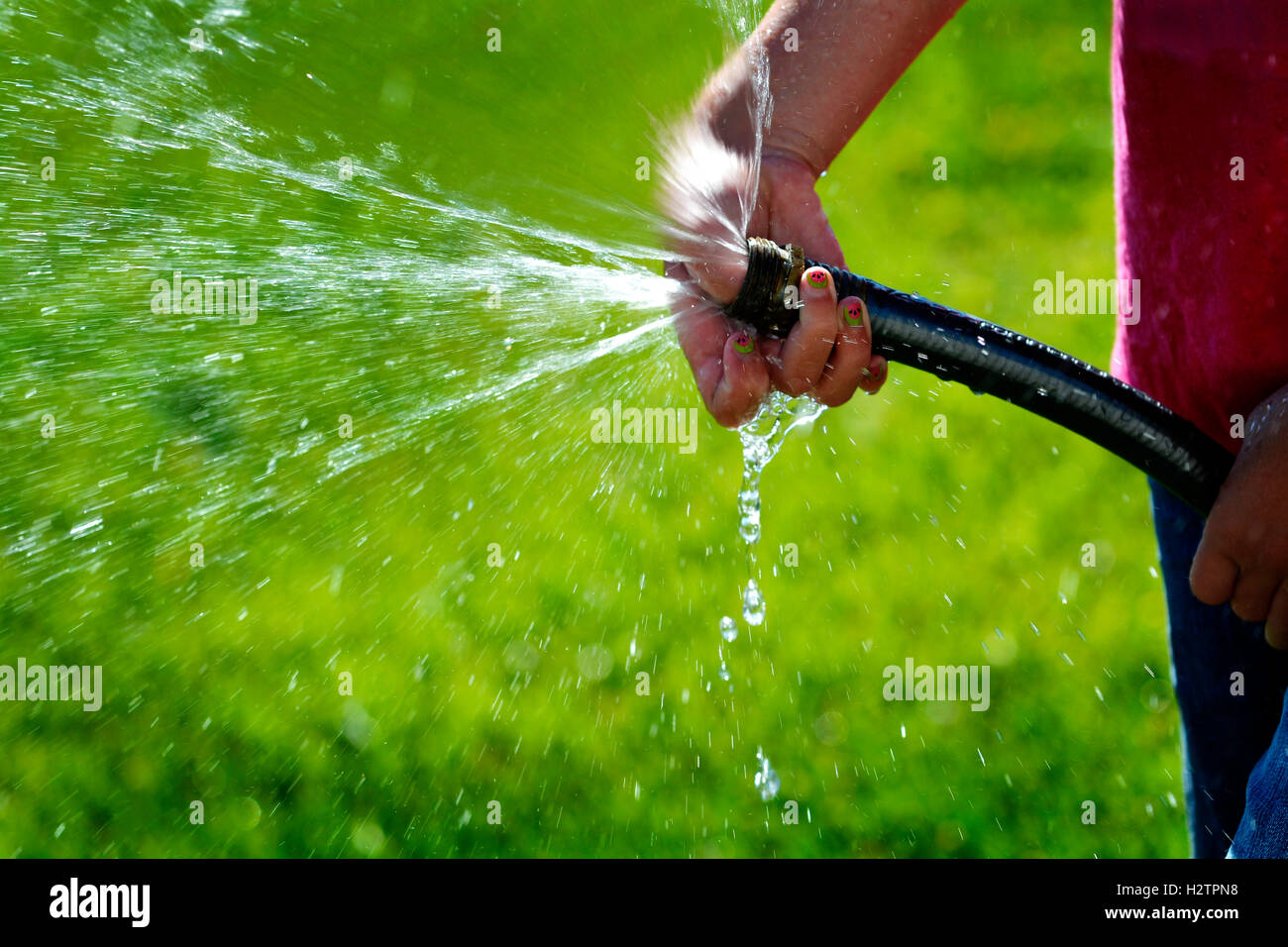 Hand And Hose Squirting Shooting Fresh Water On Green