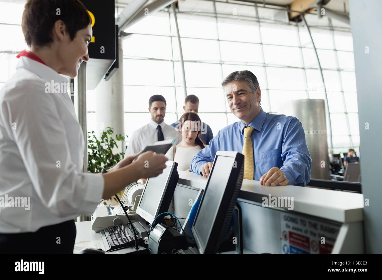 airline check in attendant handing boarding pass to passenger stock photo royalty free image. Black Bedroom Furniture Sets. Home Design Ideas
