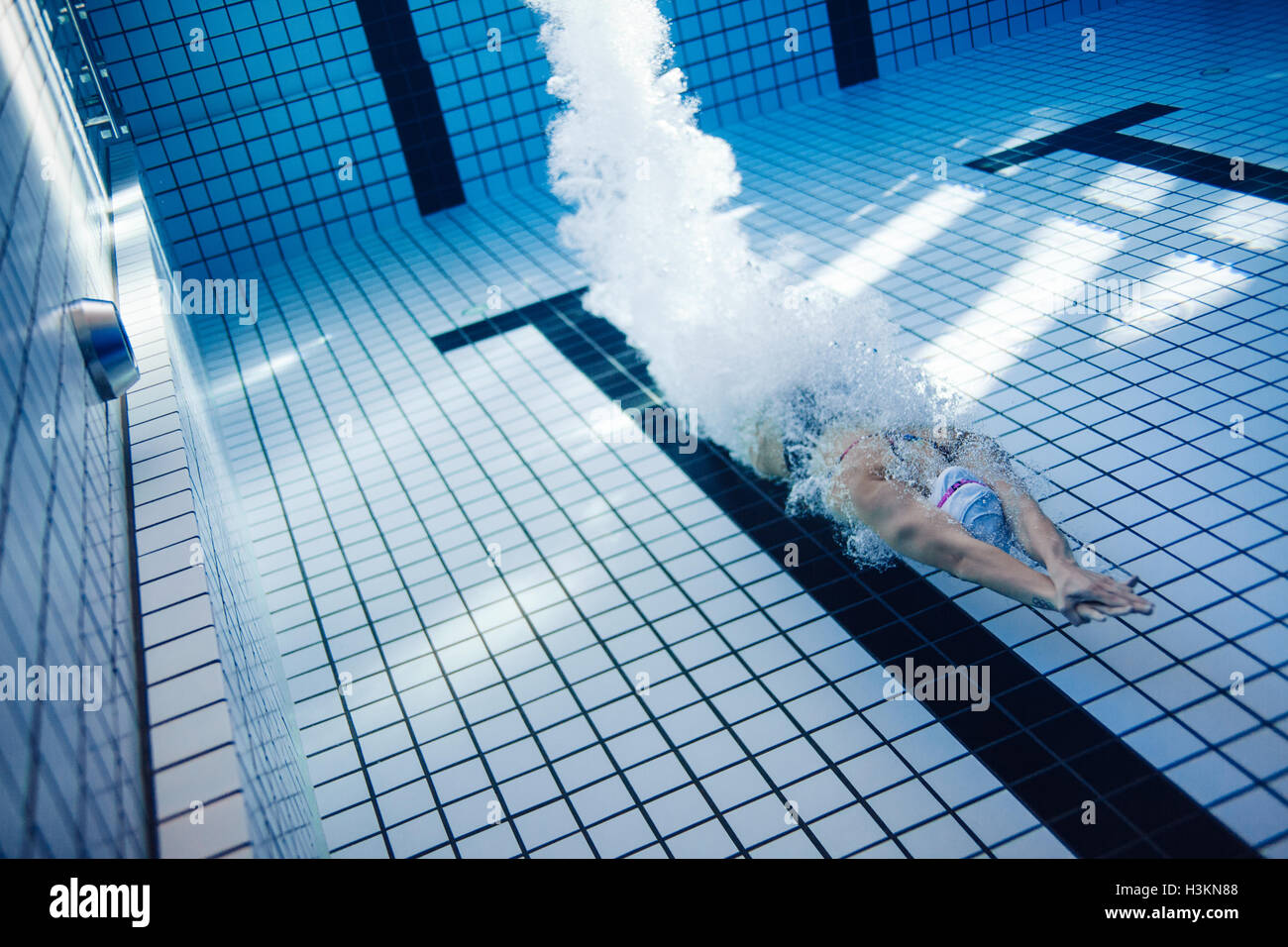 Underwater shot of female swimmer swimming inside pool. Fit young female swimmer training in the pool. Stock Foto