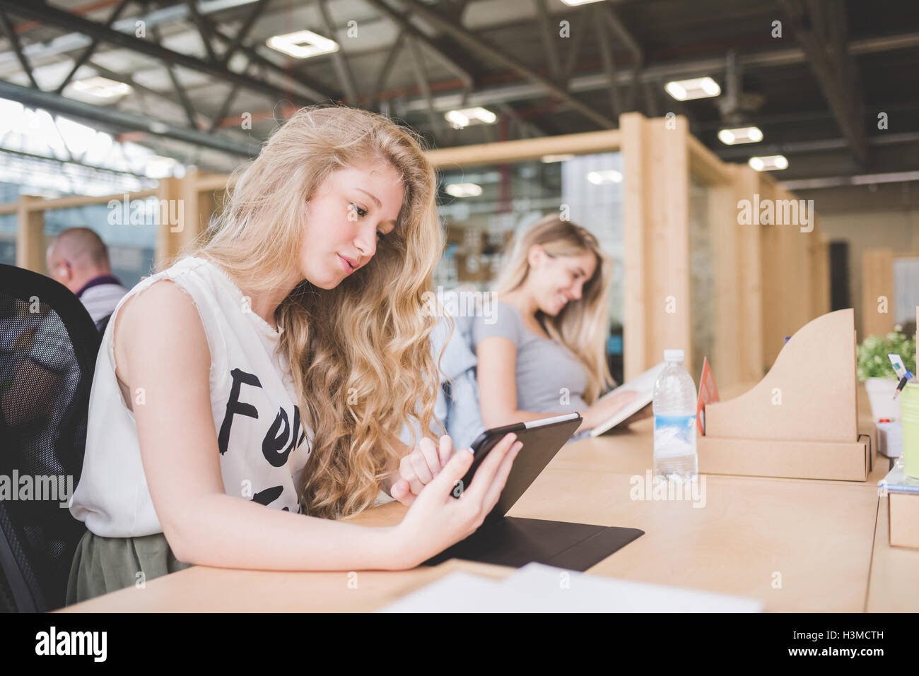 Co-workers working on digital tablet in open plan office Stock Photo