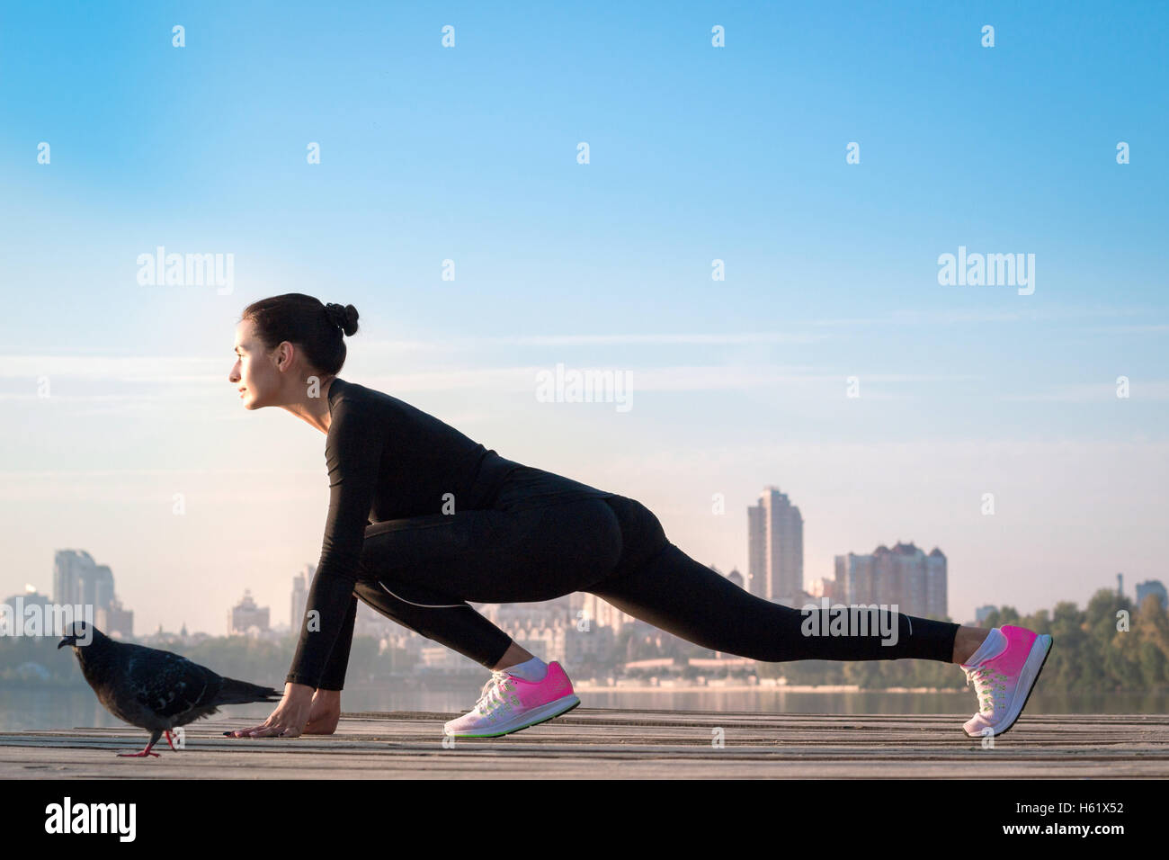 Young pretty fitness woman exercises on pier during morning sport training workout Stock Foto