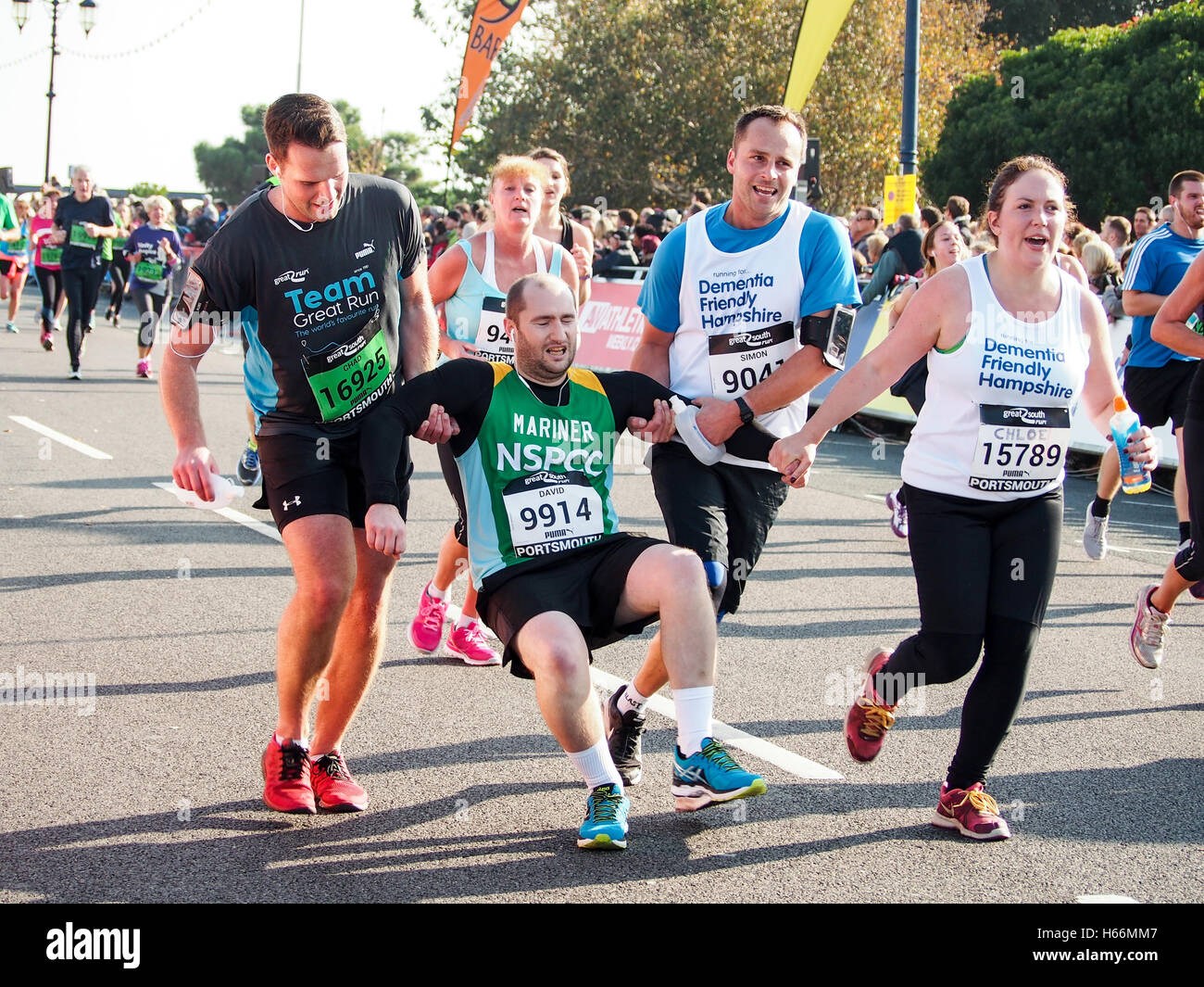 an-exhausted-runner-is-helped-towards-the-finish-line-of-the-great-H66MM7.jpg