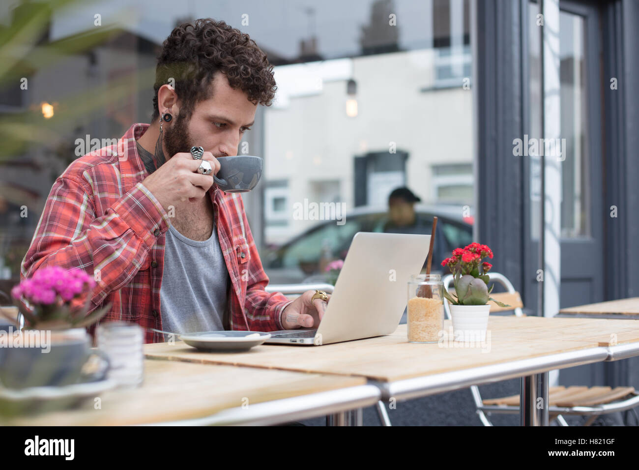 Young tattooed hipster using laptop outside cafe Stock Foto