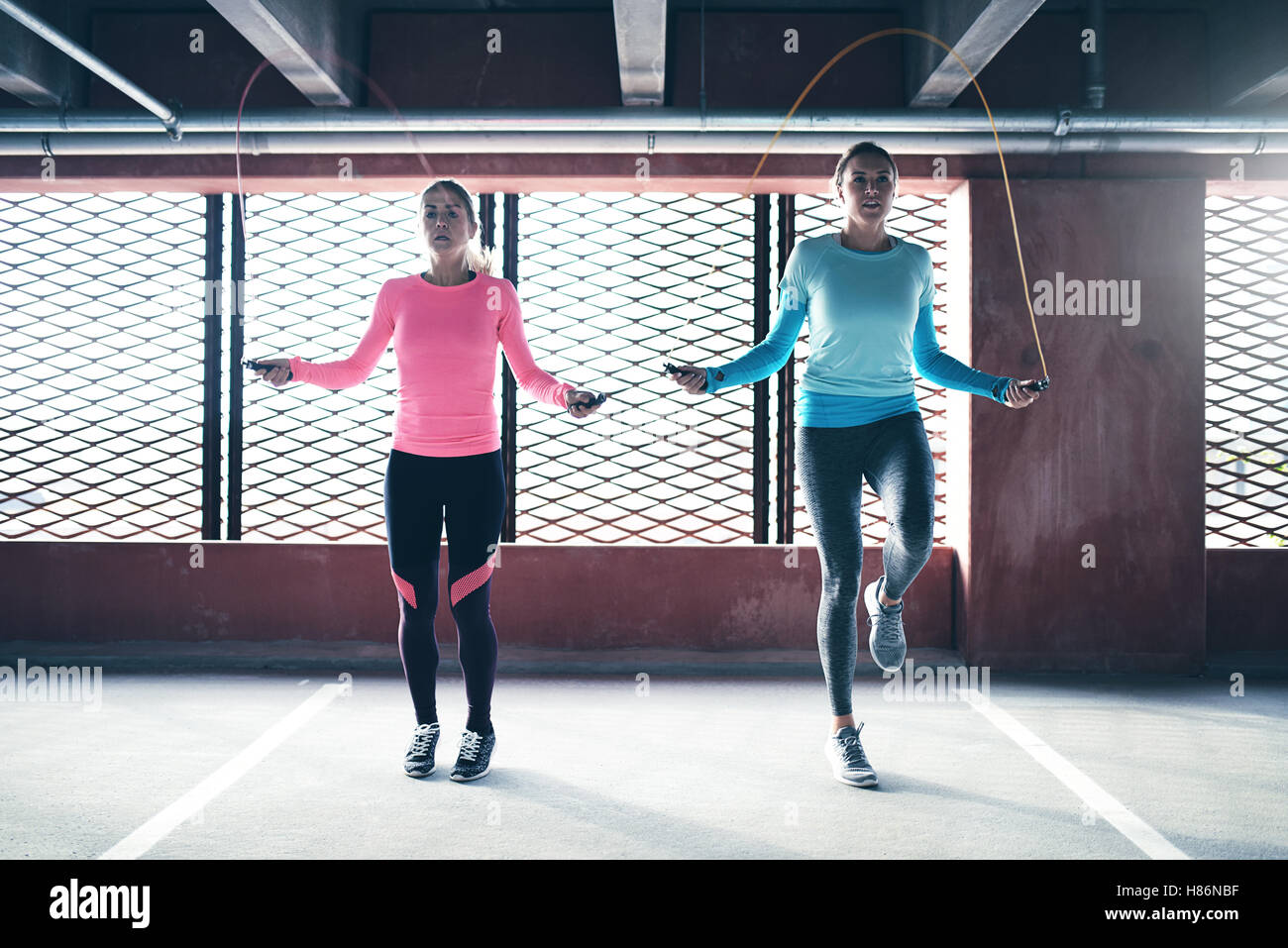 Front view of two athletic girls doing jump rope exercise. Copyspace Stock Foto