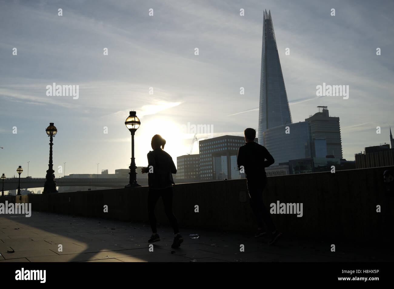 A couple running along the Thames river, London Stock Foto
