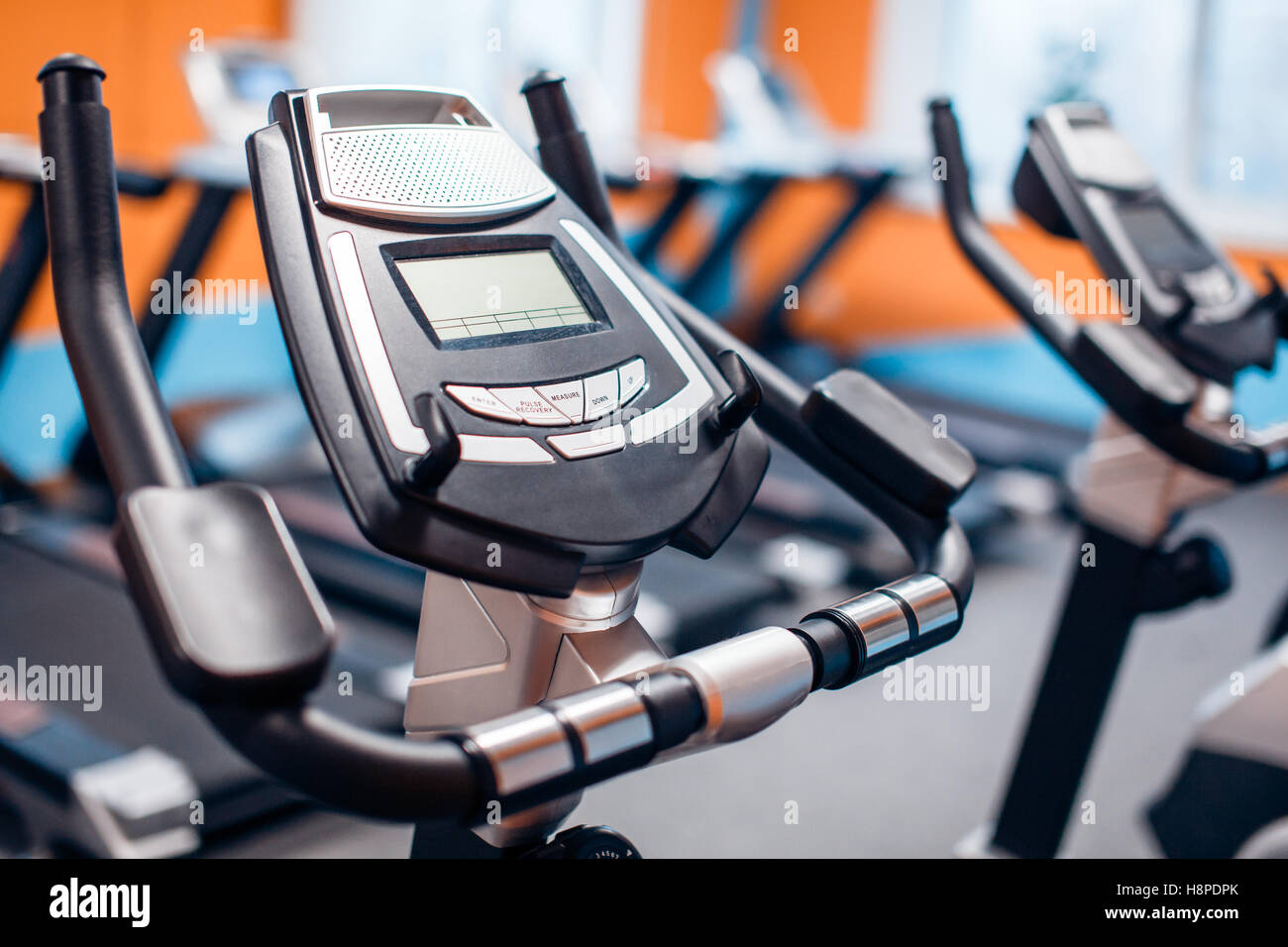 Aerobics spinning exercise bikes gym room with many in a row Stock Foto