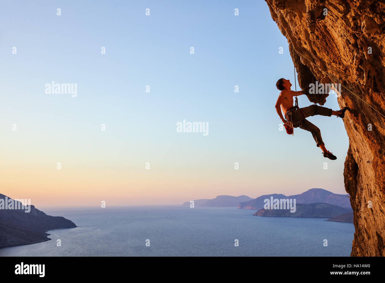 Rock climber resting while climbing overhanging cliff Stock Foto