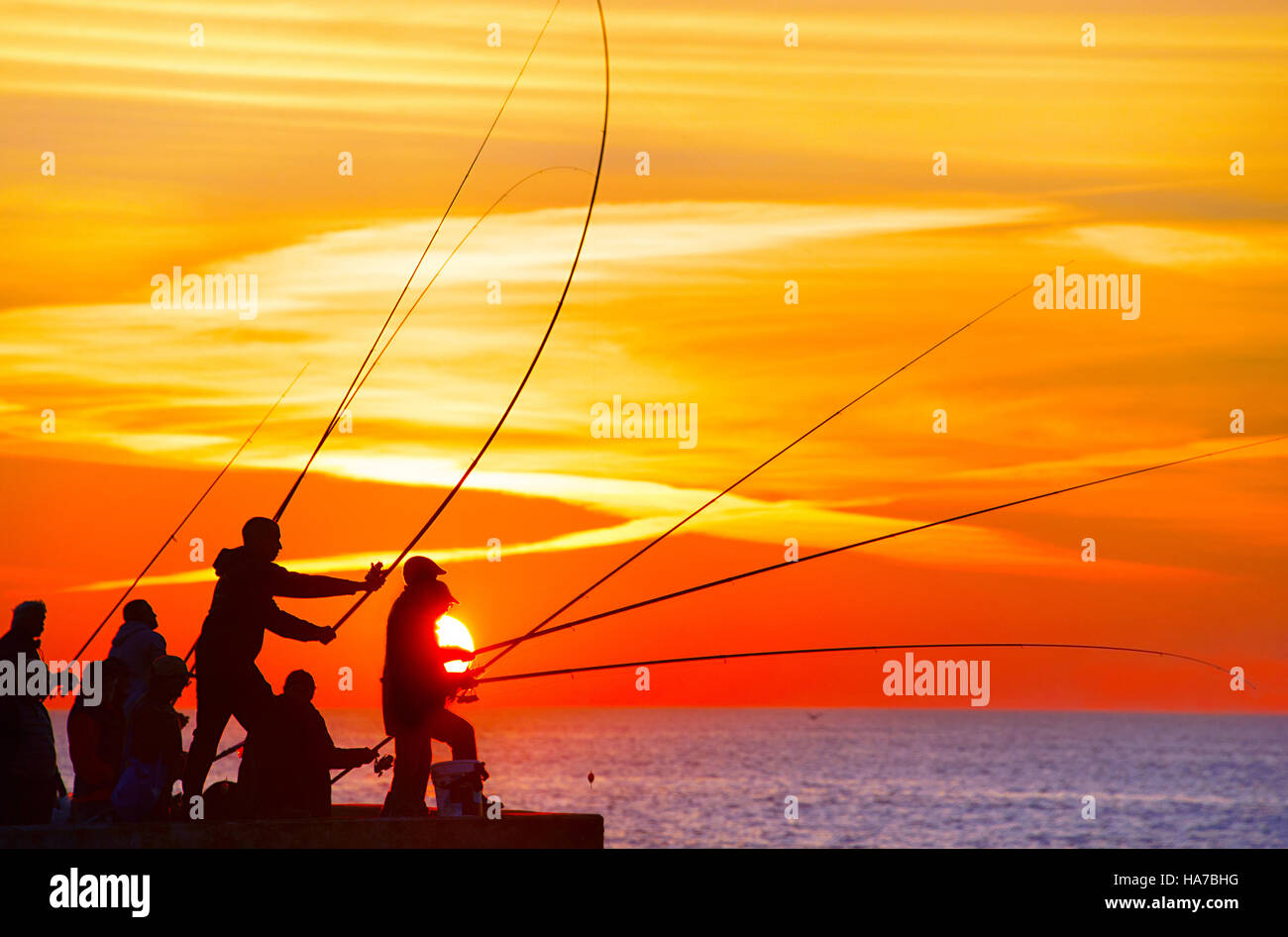 Group of fisherman on a pier at sunset. Porto, Portugal Stock Foto