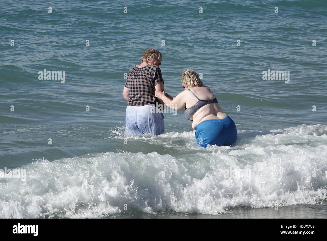 two-senior-women-playing-in-the-waves-of