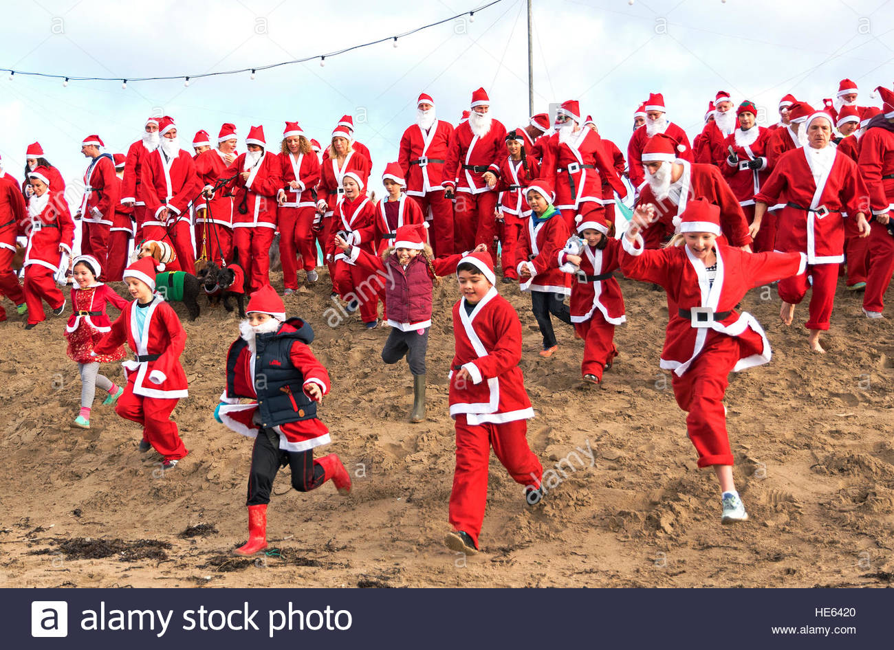 Perranporth, Cornwall, UK. 18th December 2016. Santa's on the sand an annual charity run on Perranporth beach in Stock Foto