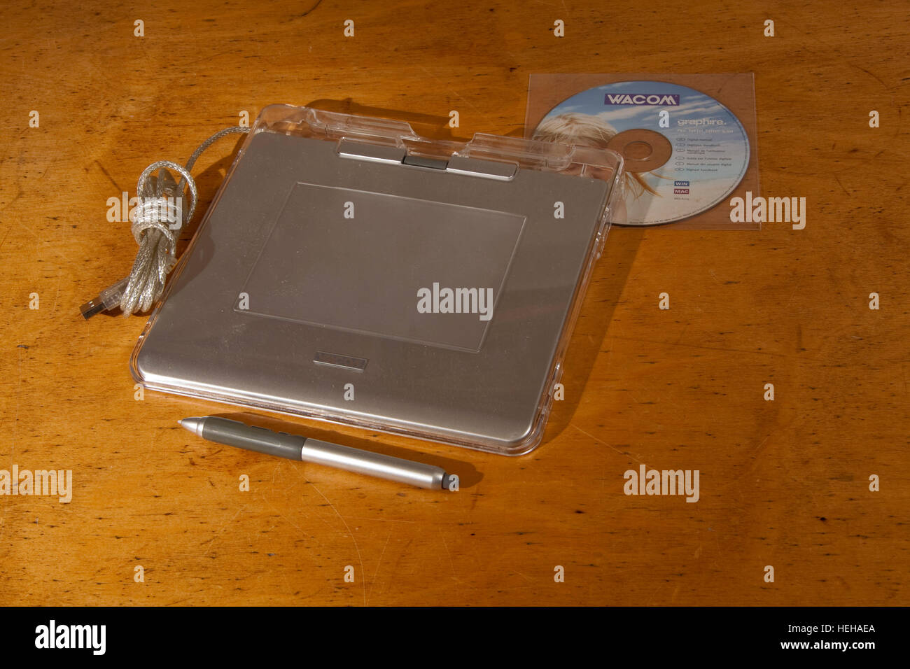 A silver graphics pen tablet on a wooden surface Stock Photo