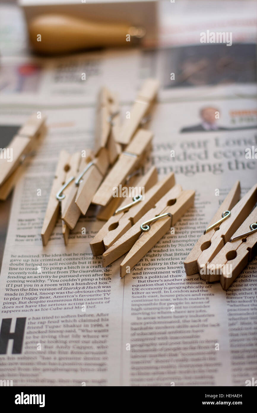 Wooden clothes pegs/clothespin on a newspaper Stock Photo