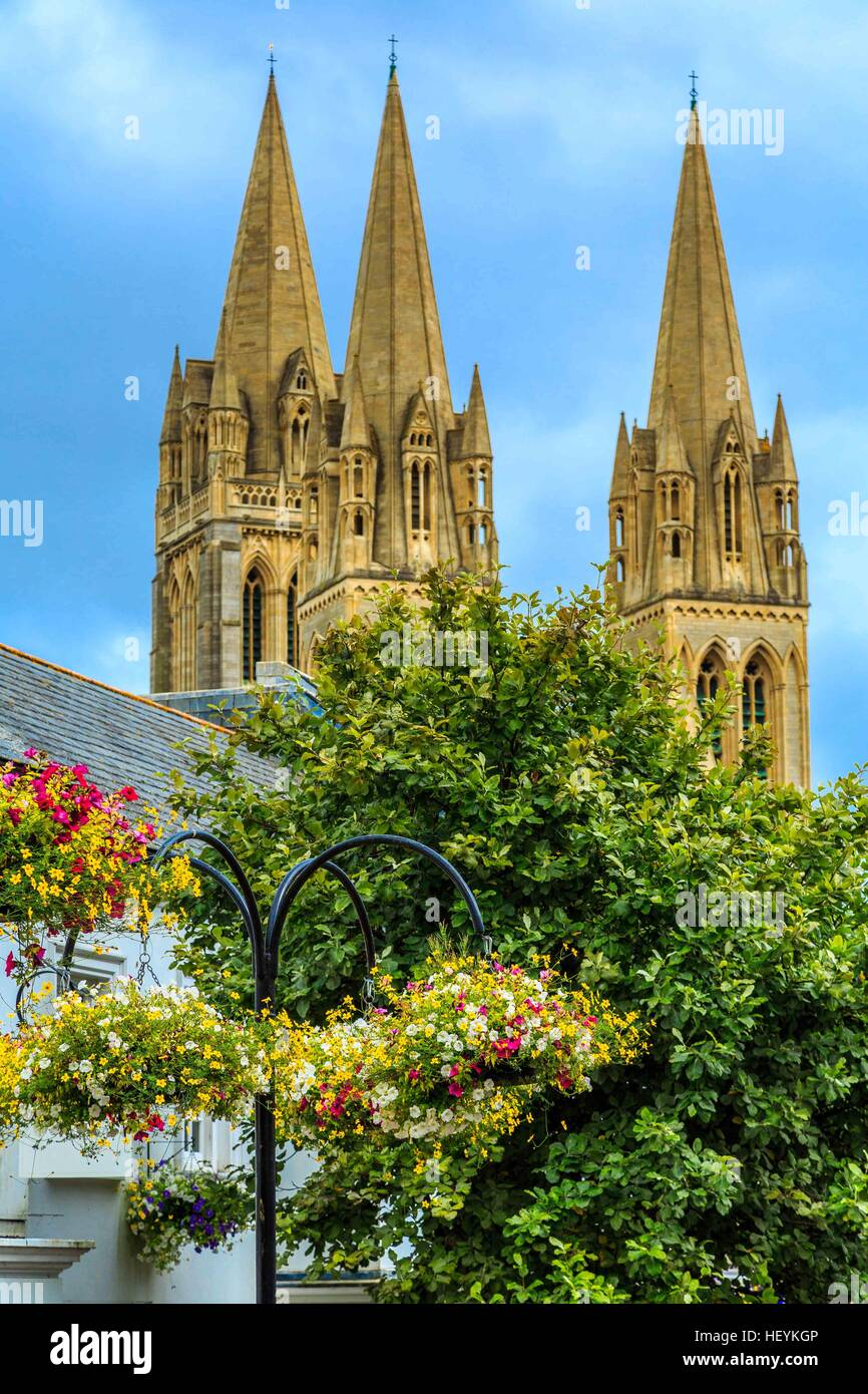 A view of Truro Cathedral spires from behind tress and flowers. Stock Photo