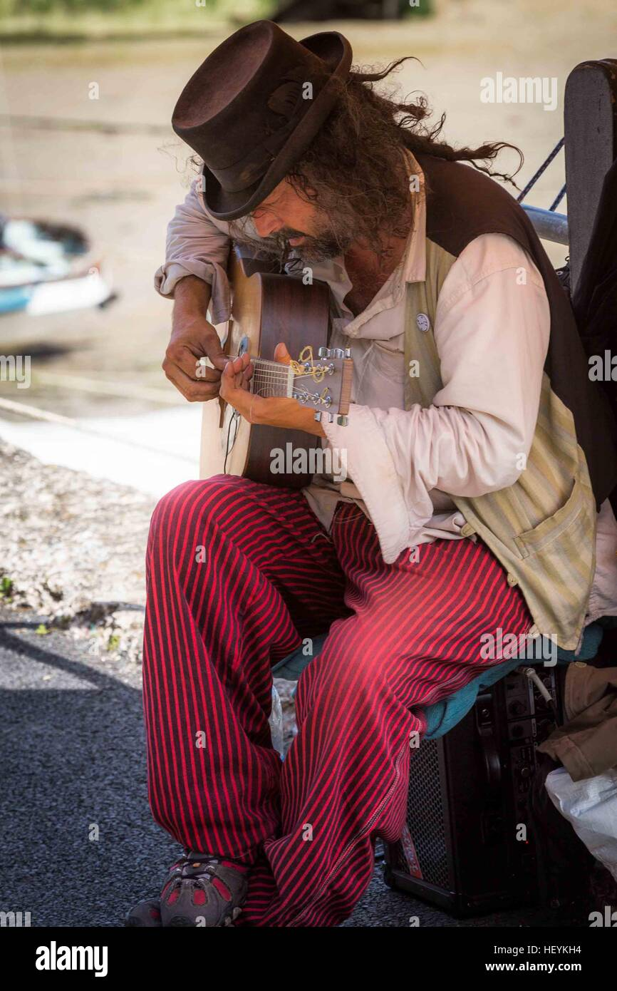 a musician busker playing acoustic guitar at Padstow Harbour in  Cornwall, UK Stock Photo