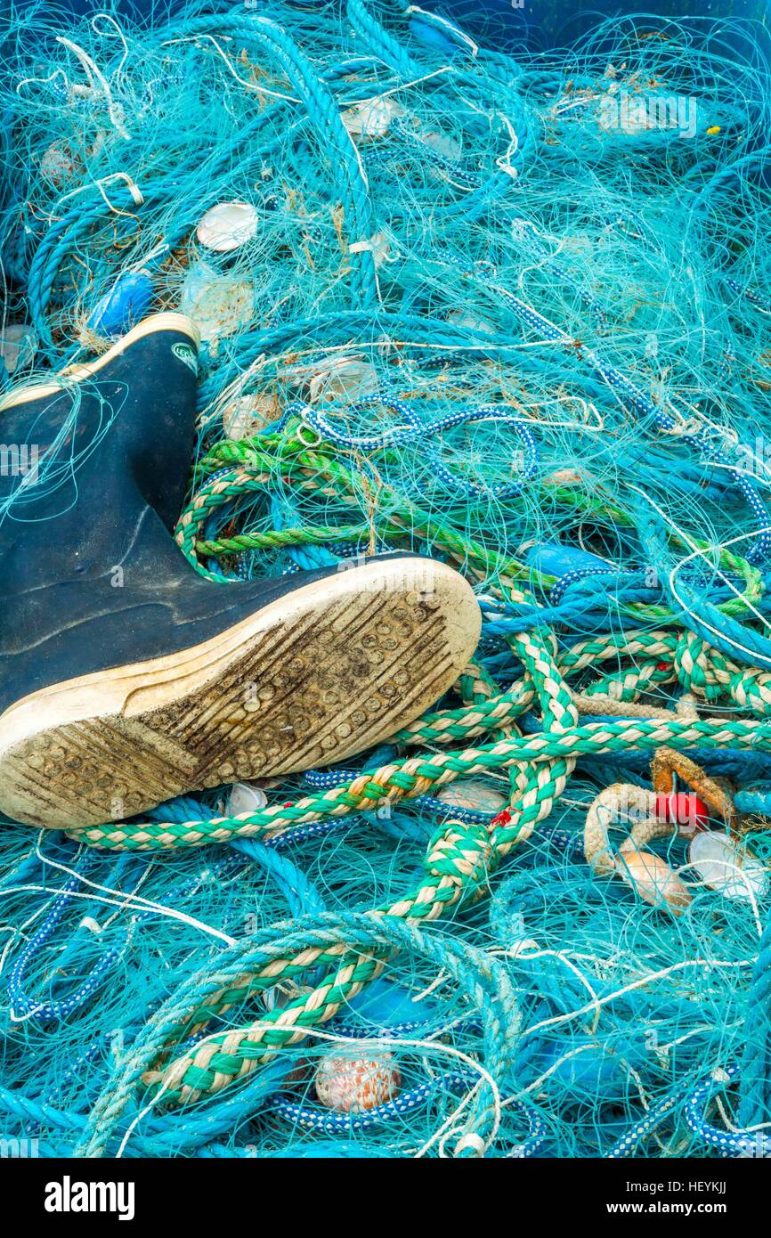 a wellington boot and a fishing net at Newquay Harbour, Cornwall, UK Stock Photo