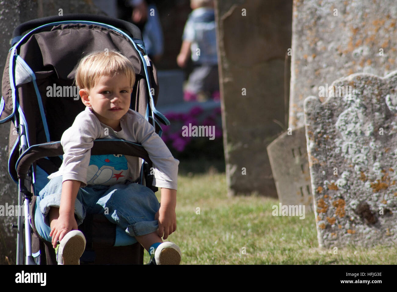 Small boy in a buggy/stroller and a churchyard looks at the camera Stock Photo