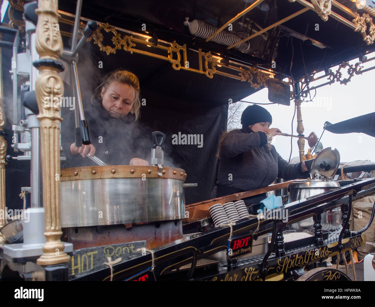 ladies-selling-hot-nuts-from-a-traditional-street-stall-at-a-christmas-HFWK8A.jpg