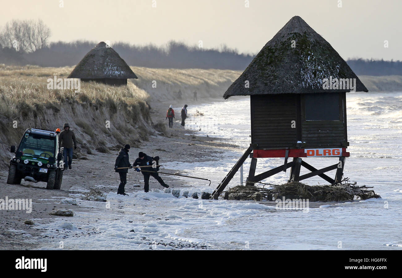 Graal-Mueritz, Germany. 05th Jan, 2017. Workers look at a severely damaged lifeguard's tower on the Baltic coast Stock Photo
