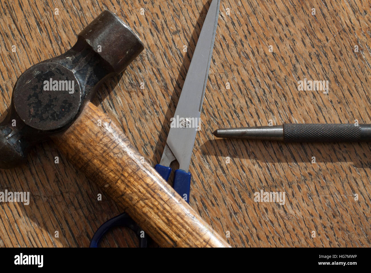 Ball pein hammer, scissors and a centre/centrer punch on a wooden surface Stock Photo